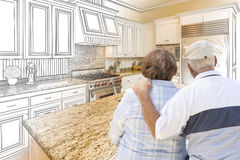 Senior Couple Looking Over Custom Kitchen Design Drawing and Pho. To Combination Stock Images