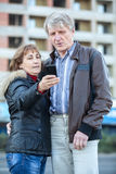 Senior couple looking at phone screen after making selfie Royalty Free Stock Images