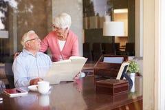 Senior Couple Looking At Photo Album Through Window Stock Photos