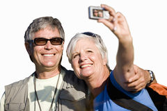 Senior couple looking at photograph on camera, cut out stock photography