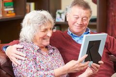 Senior Couple Looking At Photograph In Frame Together Royalty Free Stock Image