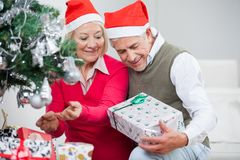 Senior Couple Looking At Present While Decorating Royalty Free Stock Photography