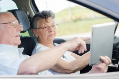 Senior couple looking at tablet in vehicle stock images