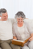 Senior couple looking at their photo album Royalty Free Stock Photos