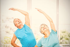 Senior couple looking up at home. Senior couple with arms raised while exercising at home Royalty Free Stock Images