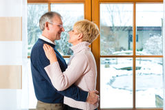Senior couple looking or of the window hugging Royalty Free Stock Image