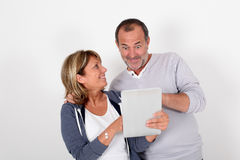 Senior couple lookint at tablet with surprised look Royalty Free Stock Photography