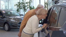 Senior couple looks inside the car at the dealership stock video