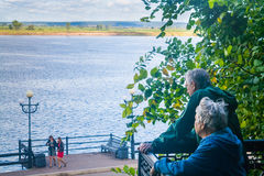 Senior couple looks at two young laughing girls. On a embankment Royalty Free Stock Photo