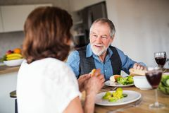 Senior couple in love having lunch indoors at home, talking. A senior couple in love having lunch indoors at home, talking stock photos