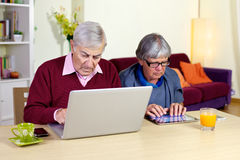 Senior couple in love with technology tablet and computer Royalty Free Stock Images