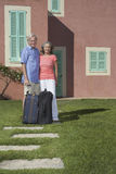 Senior Couple With Luggage In Front Of House Stock Images