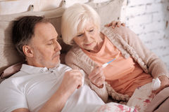 Senior couple lying on bed and checking thermamet Stock Images