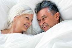 Senior couple lying in bed. Together Royalty Free Stock Images