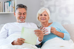 Senior couple lying in bed. Together Stock Image