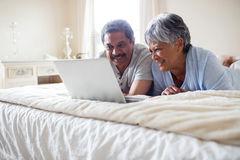 Senior couple lying on bed and using laptop Stock Image
