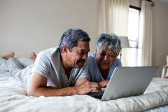 Senior couple lying on bed and using laptop Stock Photography