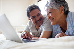 Senior couple lying on bed and using laptop Royalty Free Stock Photo