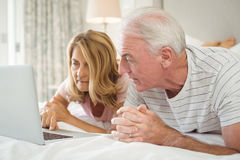 Senior couple lying on bed and using laptop Royalty Free Stock Images