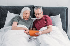 Senior couple lying in bed and using tablet together stock photography