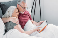 Senior couple lying in bed and using tablet together royalty free stock photos
