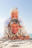 Senior couple lying down on the beach Stock Image