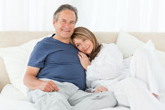 Senior couple lying down on their bed Stock Photography