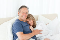 Senior couple lying down on their bed Stock Images