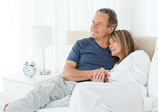 Senior couple lying down on their bed Royalty Free Stock Photography