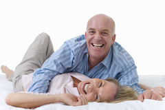 senior couple lying down together, playing, cut out Stock Image