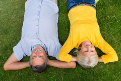 Senior couple lying on grass. Loving senior couple smiling outdoors Stock Images
