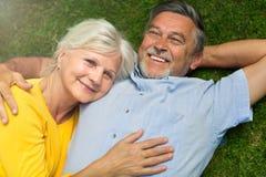 Senior couple lying on grass. Loving senior couple smiling outdoors Royalty Free Stock Photos