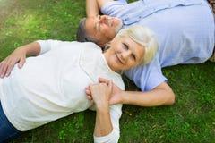 Senior couple lying on grass. Loving senior couple smiling outdoors Royalty Free Stock Images