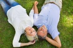 Senior couple lying on grass. Loving senior couple smiling outdoors Stock Photo