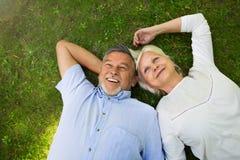 Senior couple lying on grass. Loving senior couple smiling outdoors Stock Photography
