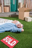 Senior couple lying on green grass between cardboard boxes and sold sign Royalty Free Stock Photo