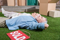 Senior couple lying on green grass between cardboard boxes and sold sign Stock Photos