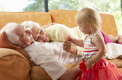 Senior Couple Lying On Sofa With Granddaughter Royalty Free Stock Photos