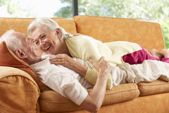 Senior Couple Lying On Sofa At Home Royalty Free Stock Images