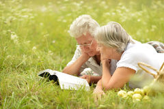 Senior couple lying in summer field Royalty Free Stock Photos