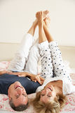Senior Couple Lying Upside Down Together In Bed Royalty Free Stock Images