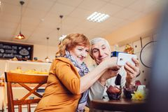 Senior couple makes a selfie using a phone in the cafe. Celebrating anniversary. Stock Photos