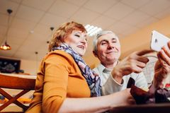 Senior couple makes a selfie using a smartphone in cafe. Celebrating anniversary. Retired people having fun. Senior couple makes a selfie using a phone incafe Stock Image