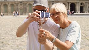 Senior couple making selfie with smartphone on vacation in Paris, having fun traveling together. Senior couple making selfie with smartphone on vacation in Paris stock video