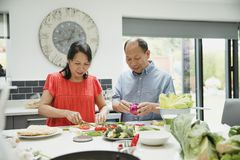 Senior Couple Making a Stir Fry Together. Senior couple are preparing vegetables together in the kitchen to make a stir fry royalty free stock photo