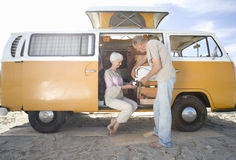 Senior couple making tea in camper van on beach Royalty Free Stock Images
