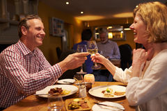 Senior couple making a toast at a meal in a restaurant Stock Photo