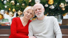 Senior couple in mall during holiday season. Loving hugging pensioners in shopping center smiling. Portrait of senior couple sitting in mall looking at camera stock footage