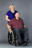 Senior couple with man in wheelchair. Happy senior couple with old men in a wheelchair, studio shot on grey Royalty Free Stock Photography