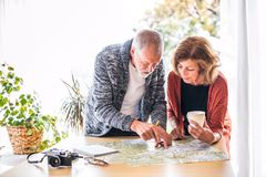 Senior couple with map at home, making plans. Royalty Free Stock Photo
